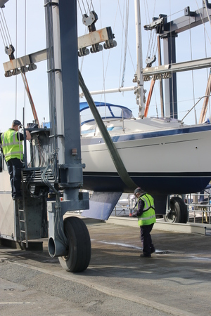 lowered: 14TH MARCH 2017,CHICHESTER,ENGLAND: A yacht getting ready to be lowered into the water using a boat cradle sling in chichester