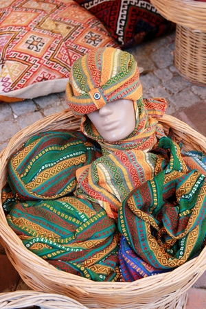 A mannequin head wearing a hat for sale in a basket, 2017
