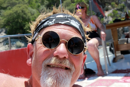 An englishman with a beard wearing a bandana and cool sunglasses while on vacation, 2017 photo