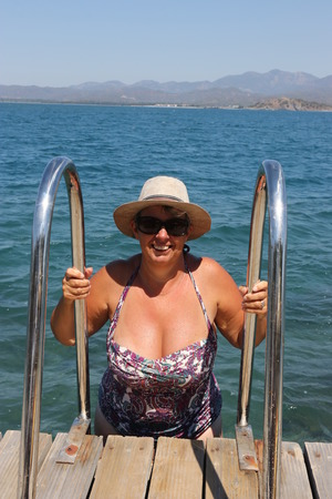 A buxom mature english lady getting out of the sea using ladders on the jetty while on vacation in turkey 2017 Editorial