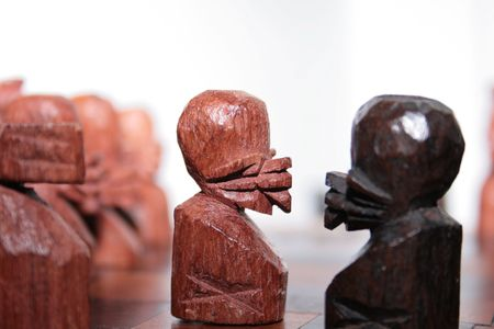 two native african pawns of a handmade chess opposing at the board