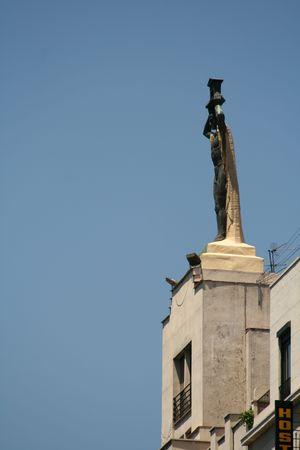 art deco statue on roof in Gran Via Street in Madrid photo