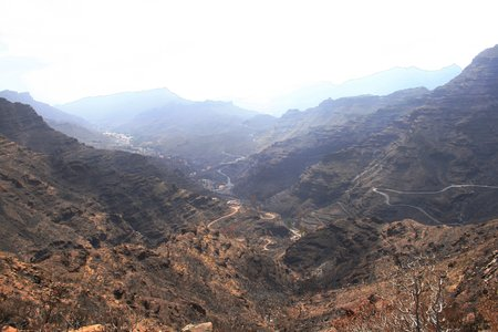 road curves amongst the burnt forest of Mogan gorge, Canary Islands Stock Photo