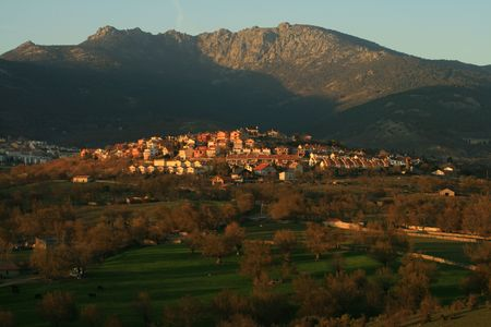 Cercedilla town in new national park atop farming hill with mountain range in background