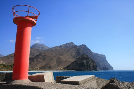 lighthouse at the entrance of the tropical port of san nicolas in the canary islands