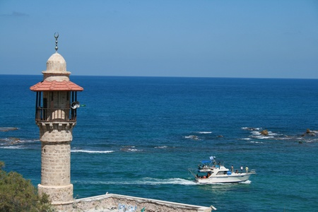 mosque tower in old Jaffa overseeing the Mediterranean sea and boat