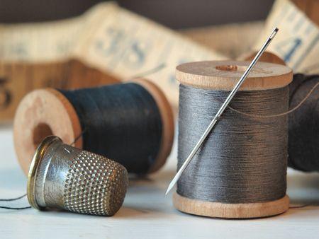 Close up de bobinas de hilo, aguja y dedal con una cinta métrica en segundo plano.