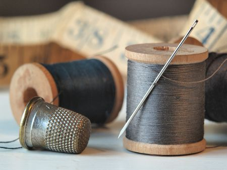 needle and thread: Close up of thread spools, needle, and thimble with a tape measure in the background. Stock Photo
