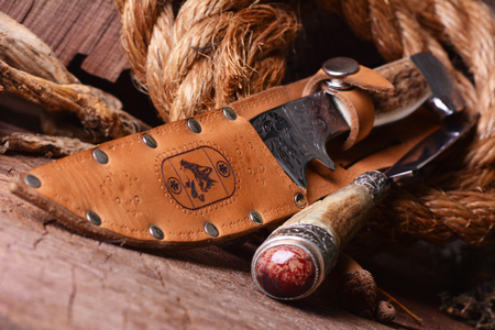 Hunting knife on a wooden background