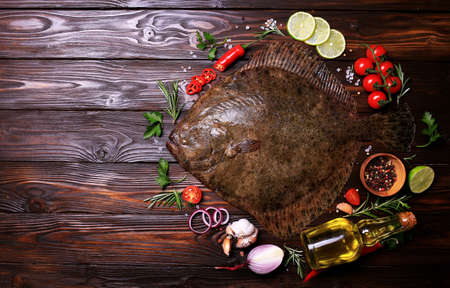 Halibut fish on wood background with spices and vegetables