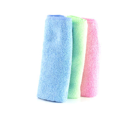 Pink, blue and green towels roll standing vertically on a white background photo