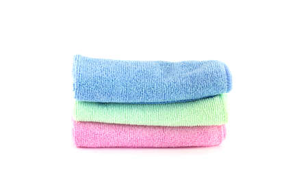 Pink, blue and green towels roll horizontally on a white background photo