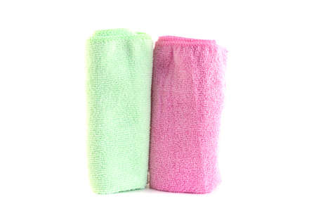 Pink and green towels roll standing vertically on a white background photo