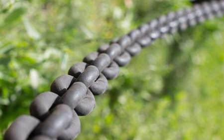 confine: Iron black chains on grass background