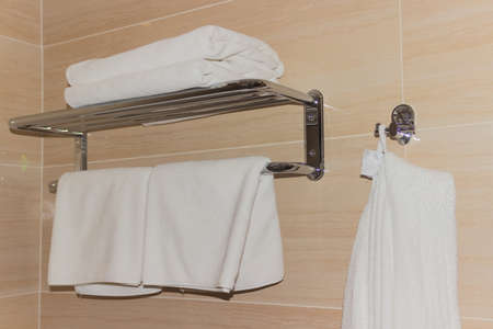 absorb: White towels and a bathrobe in the bathroom on steel shelves Stock Photo