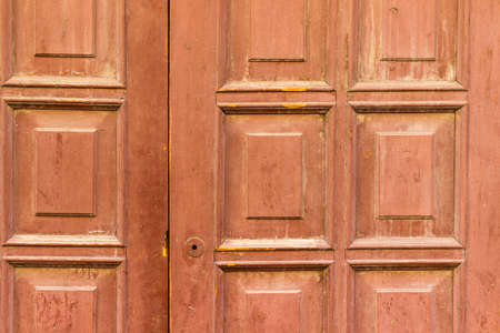 panelled: Wooden red door close up with ornament