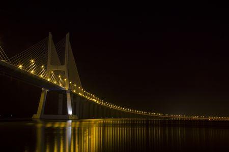 Lange Vasco da Gama Br�cke �ber den Tejo bei Nacht zu h�ngen, in Lissabon Lizenzfreie Bilder