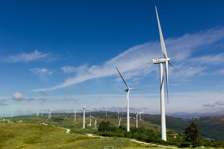 View of a wind farm with a blue sky and clouds.