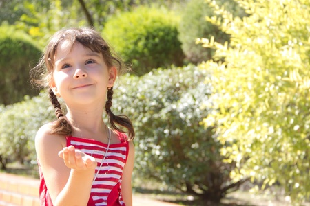 Little girl sends an air kiss and smiling Stock Photo