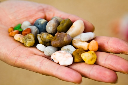 Small stones in hand on sea coast