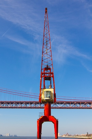 red crane and red metallic bridge on background