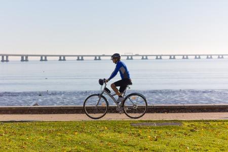 Man biking along river