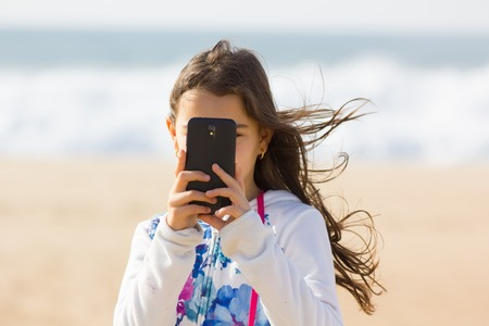 Cute Girl taking photo with cellphone on the beach, sea background. Zdjęcie Seryjne