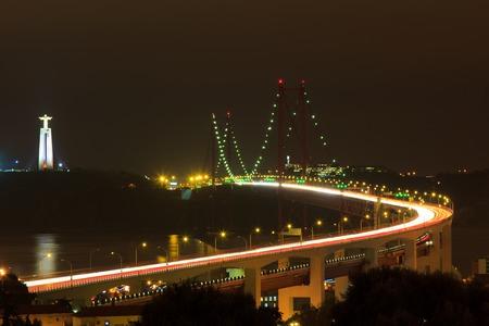 The 25 De Abril Bridge in Lisbon over Tagus River (Ponte 25 de Abril) at night motion blur Stock Photo