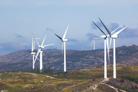 View of a wind farm with a blue sky and clouds