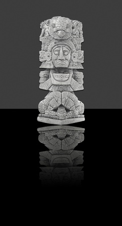 Mexican statue - isolated against black and grey background photo