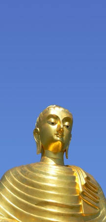 Golden buddha statue in Thailand, isolated against blue sky photo