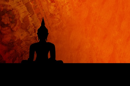 Black buddha silhouette, isolated against colorful orange-red background (incl. clipping path) photo