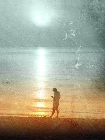 Sad man standing at the beach at sunset photo