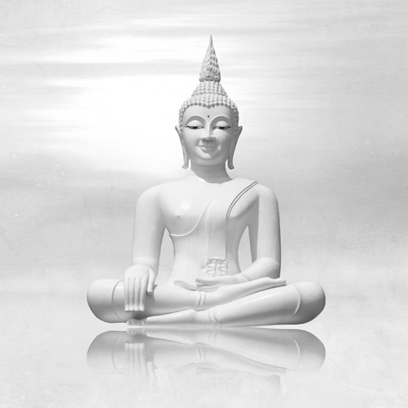 White buddha in lotus position against light grey sky background - meditation concept Stockfoto