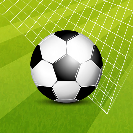 Soccer ball in net on grass field background
