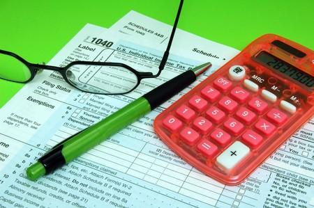 podatnika: Federalny podatek Formularze z długopisem i Kalkulator na zielonym tle