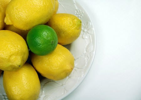 Lemons and Lime with white embossed plate on white table cloth Banco de Imagens