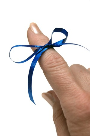 Blue ribbon tied around finger as a reminder on white background photo