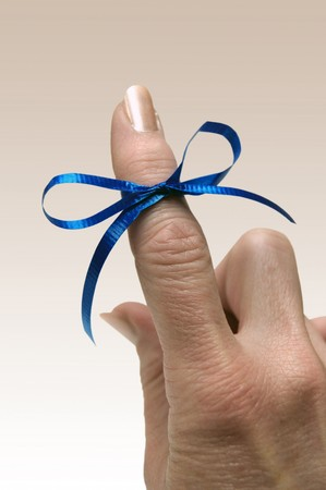 Blue ribbon tied around finger as a reminder