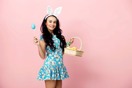 Happy easter! Beautiful sexy young woman wearing bunny ears on Easter day and holding basket with Easter eggs. Pretty girl preparing for Easter