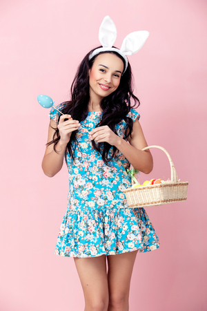 Happy easter! Beautiful young woman wearing bunny ears on Easter day and holding basket with Easter eggs. Pretty girl preparing for Easter.