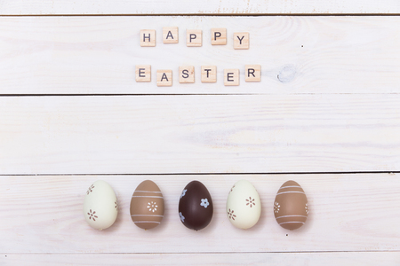 Happy Easter! Easter eggs Painted in pastel colors on white wooden background. Top view with copy space