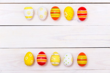 Happy Easter! Easter Colorful eggs on white wooden background. Top view with copy space