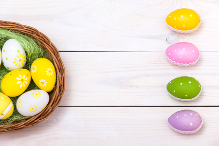 Happy Easter! Easter eggs in nest on white wooden background. Top view with copy space