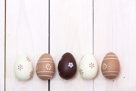 Happy Easter! Easter eggs Painted in pastel on white wooden background. Top view with copy space