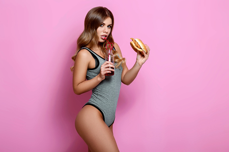 Beautiful female fitness model. Sexy sporty young girl with an excellent body appetizingly eats a great delicious burger. Perfect Sport or diet concept photo. Space for your text
