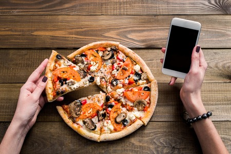 hands of a woman ordering pizza with a device over a wooden workspace table. All screen graphics are made up. Archivio Fotografico