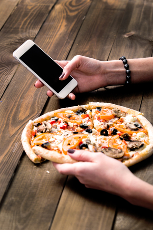 hands of a woman ordering pizza with a device over a wooden workspace table. All screen graphics are made up. Standard-Bild