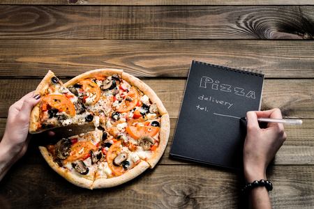 Close-up of pizza and notebook with the text: Pizza delivery. background wooden table. Notebook black with white text Archivio Fotografico