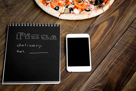 Close-up of pizza, a mobile phone and a notebook with the text: Pizza delivery. background wooden table. Notebook black with white text